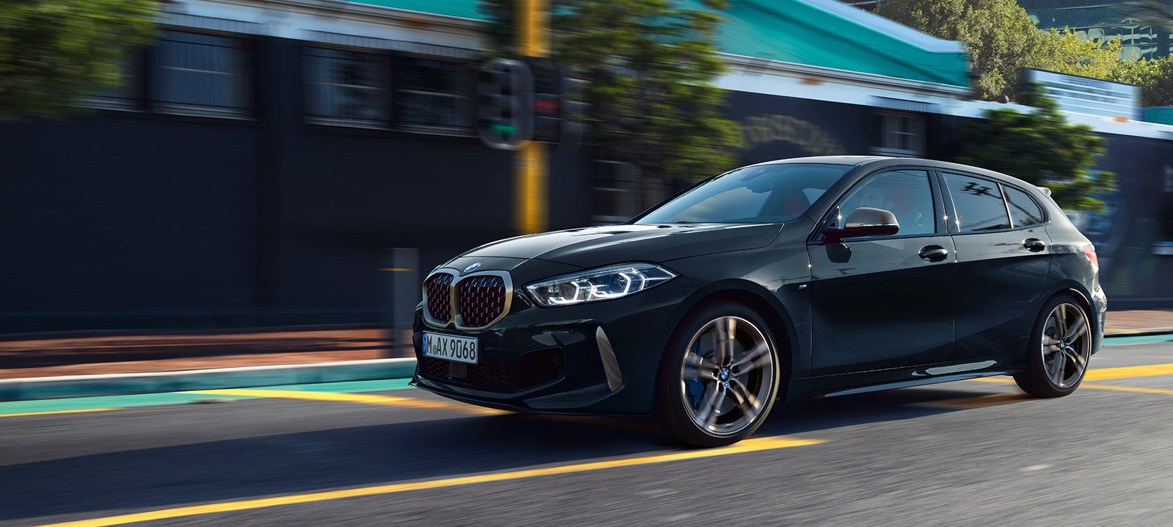 The all-new BMW M135i xDrive in Black Sapphire metallic, three-quarter side view driving.