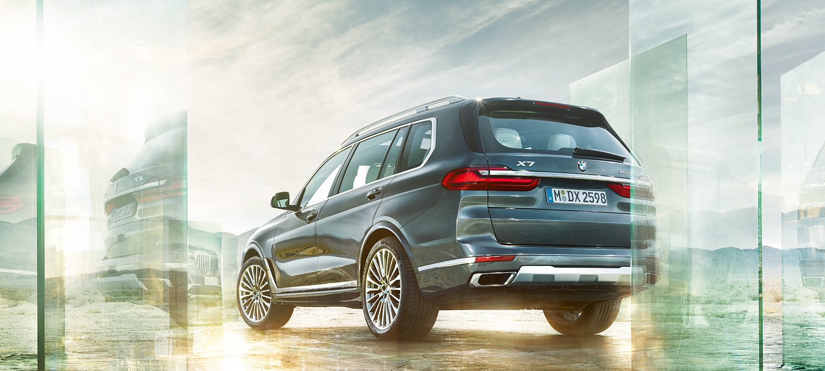 BMW X7 in Arctic Grey from three-quarter rear view in front of desert landscape, G07 2019